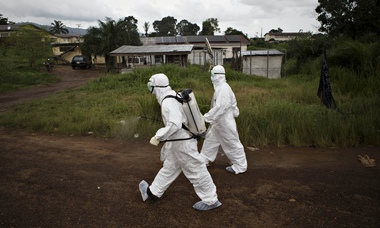 Healthcare workers spray disinfectant to prevent the spread of the Ebola virus in Kenema