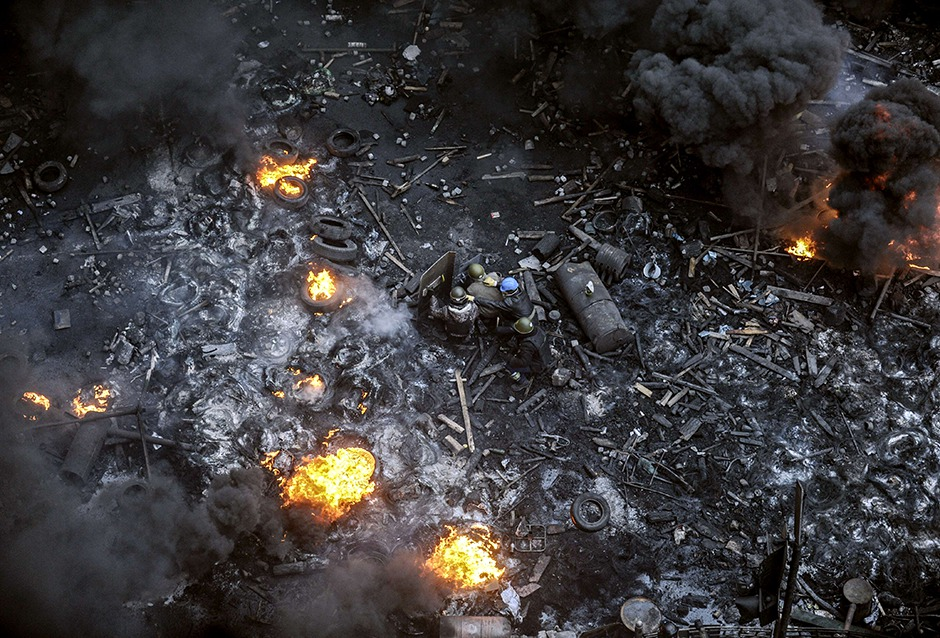 Protesters pick their way through burning barricades in Kiev