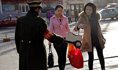 A security officer scans a pedestrian with a detector on a street in Urumqi