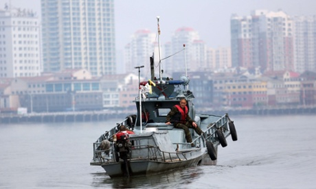 A North Korea soldier sits on a patrol boat on the Yalu River which separates the North Korean town of Sinuiju from the Chinese border town of Dandong.