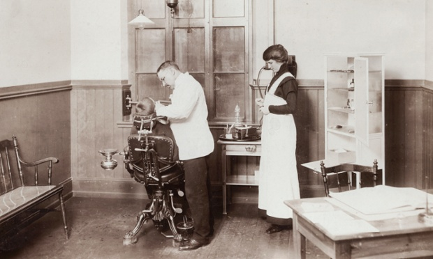A dentist and his nurse treating a schoolboy circa 1910