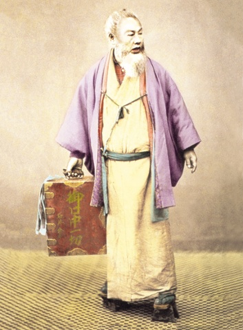 A Meiji period Japanese travelling dentist carrying the tools of his trade on his back circ 1897