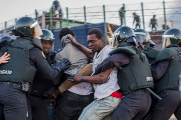 African migrants are surrounded by Spanish Civil Guard officers.