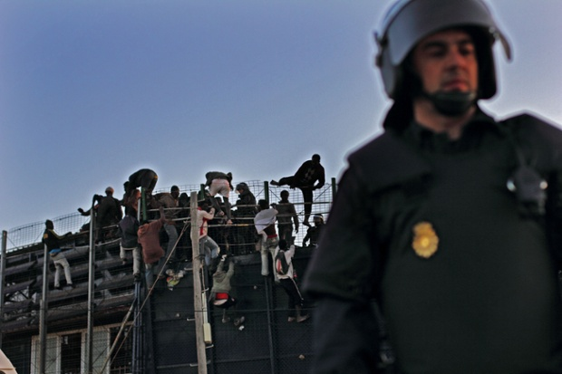 Spanish Civil Guard officers guard stand as migrants scale a fence.