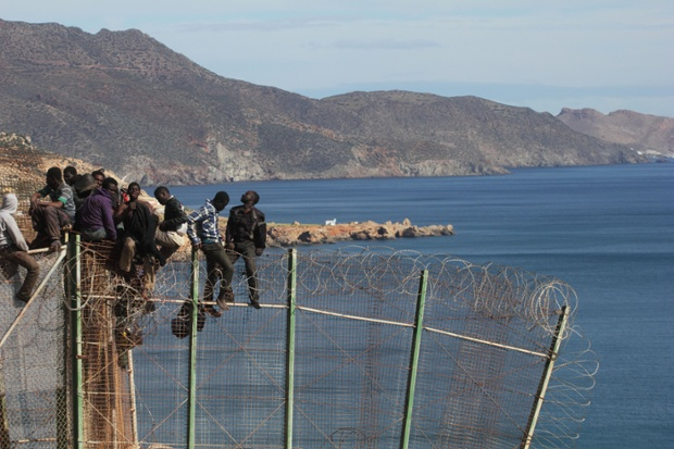 Migrants sit on top of a border fence covered in razor wire during their latest attempt to cross into Spanish territory, in April.