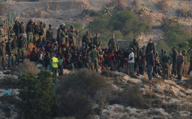 Spanish Guardia civil surround would-be immigrants who tried to scale a border fence on June 18.