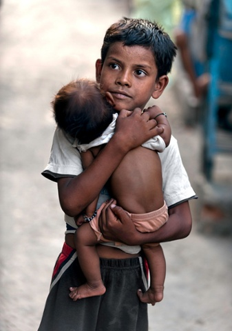Vishal Singh, aged 6, cares for a baby girl while her mother is away, in the Kusum Pahari slum in south Delhi, India. Vishal is lucky in one way, when he is not working he is able to attend a school for slum children.