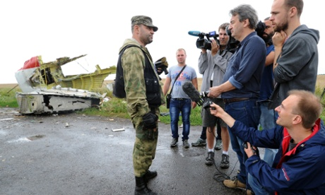 An armed pro-Russia militant attempts to stop journalists from accessing the site of the crash.