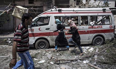 Two Palestinian girls run past a damaged ambulance in Gaza