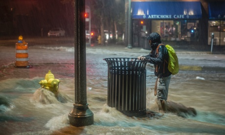 A pedestrian hangs on to a trash can along Central Avenue as rainwater flows towards downtown Albuquerque, N.M.,  August 1, 2014.  Heavy rains late Friday night caused the flash flooding and road closures in parts of downtown and in other areas.