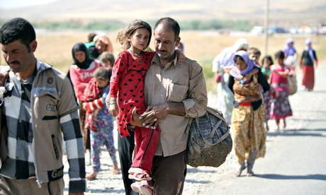 A displaced Yazidi Iraqi carries his daughter as they cross the Syrian border at Fishkhabour.