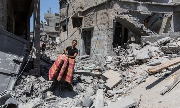 A boy in Beit Hanoun carries items collected from the rubble of his house during a 72-hour ceasefire
