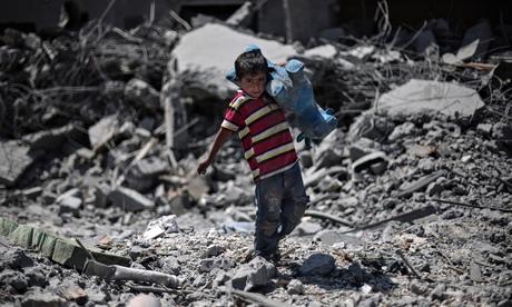 Palestinian boy walks through debris