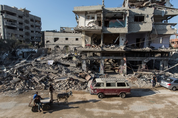 A family examines the devastation of their  apartment block in the Shuja'yya neighbourhood to the east of Gaza city.