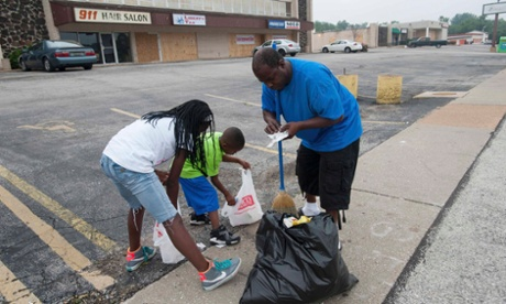 Tyrell Mosley and his daughter, McKayla and son Demarre clean up debris along West Florissant Ave. in Ferguson, Missouri.