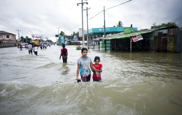 Residents walk along a flooded street in the Bago township in Burma
