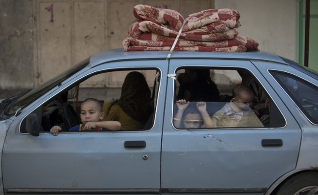 Palestinian families leave their homes in the Shujai'iya neighbourhood, Gaza