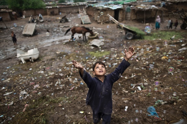 An Afghan refugee child chases bubbles on the outskirts of Islamabad, Pakistan