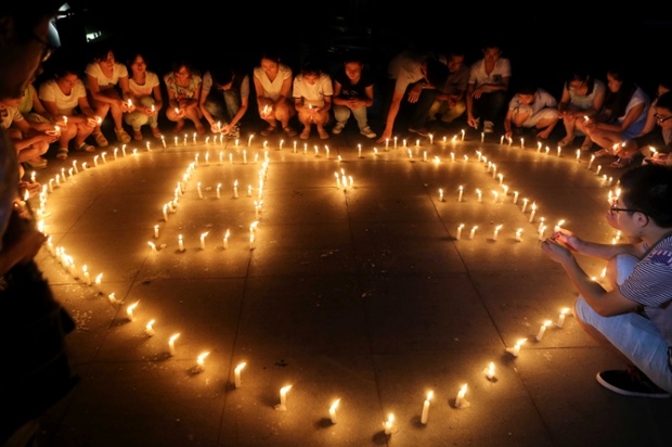 People hold candles for victims of the Yunnan earthquake in Ma'anshan, China