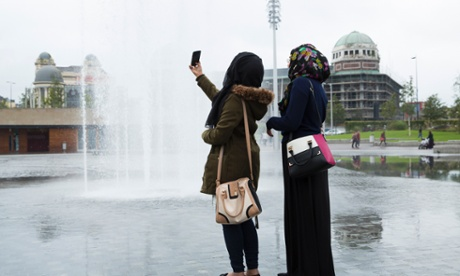 Thomond.  BRADFORD, 15th September 2014 - Young women taking selfies in City Park in the heart of Bradford city centre which is undergoing a regeneration phase led by the construction of the Westfield's shopping centre, The Broadway Bradford, due to open in late 2015 after years of delays and setbacks.