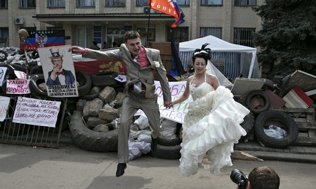 A bride and groom in front of a regional government building seized by pro-Russians in Kramatorsk