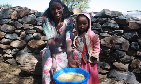 Fana Fesseha and her three-year-old daughter with bucket of honey