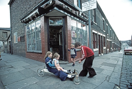 Children playing on a home-made go-cart outside a corner shop in Manchester, 1977.