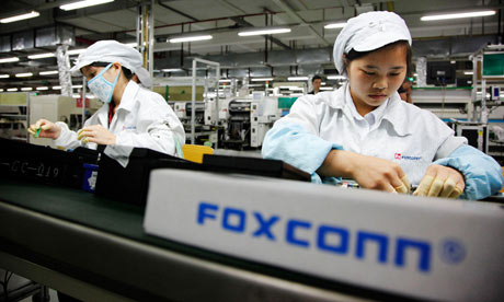 Employees work on the Apple assembly line at the Foxconn plant