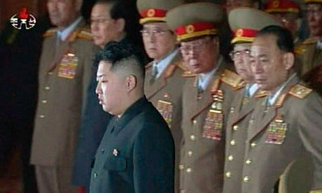 The new North Korean ruler Kim Jong-un pays his respects to his father, Kim Jong-il, lying in state