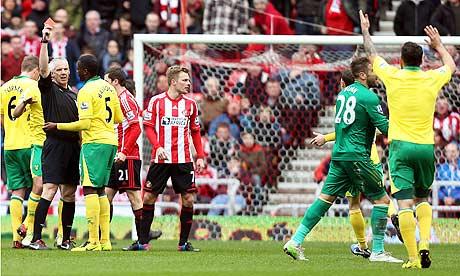 Chris Foy shows Mark Bunn the red card