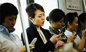 Japanese commuters watching TV on their mobiles
