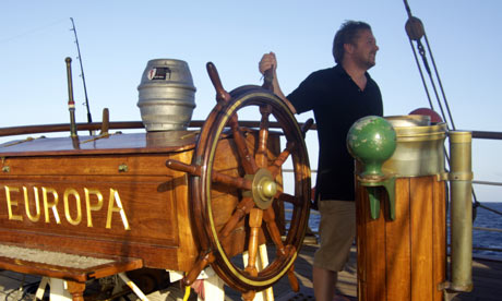 Pete Brown on the helm of Europa, with a barrel of beer