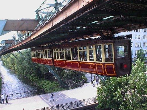 Trenul agățat sau Schwebebahn inaugurat în 1901 și cu o lungime de 13 km, circulă mai ales suspendat peste râul Wupper (Fotografie: Wikipedia).