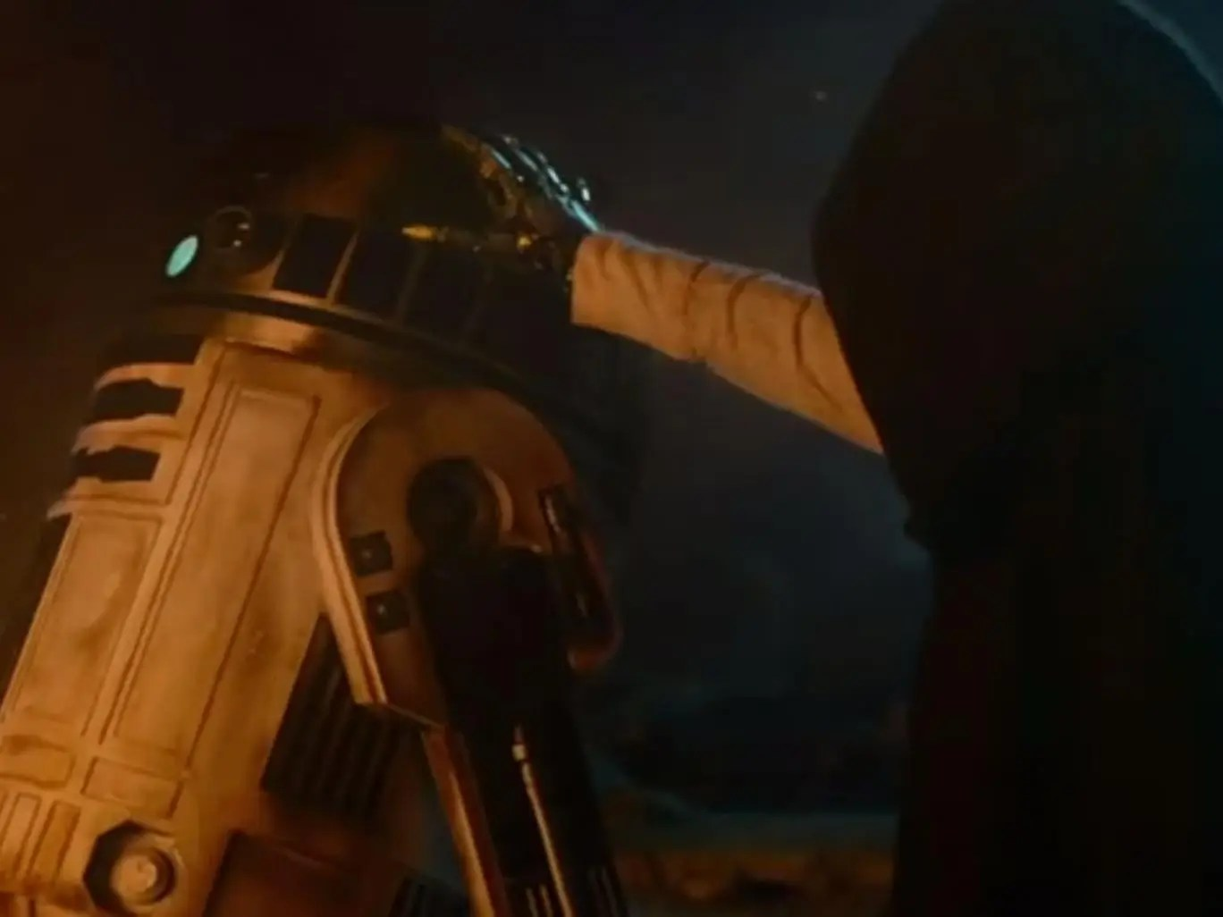 A mysterious hooded figure touches R2D2 in the latest trailer