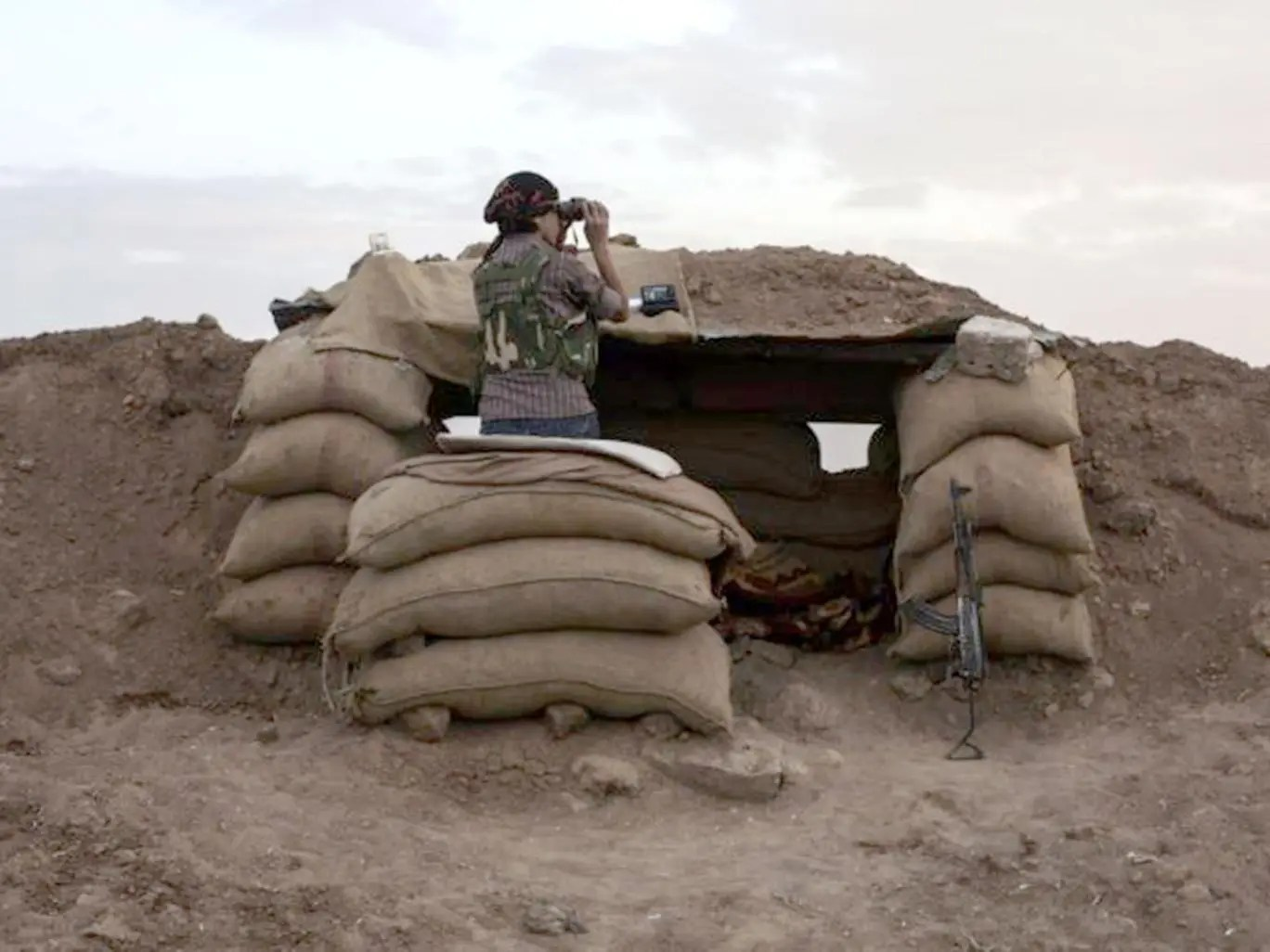 A Kurdish fighter surveys the border between Turkey and Iraq