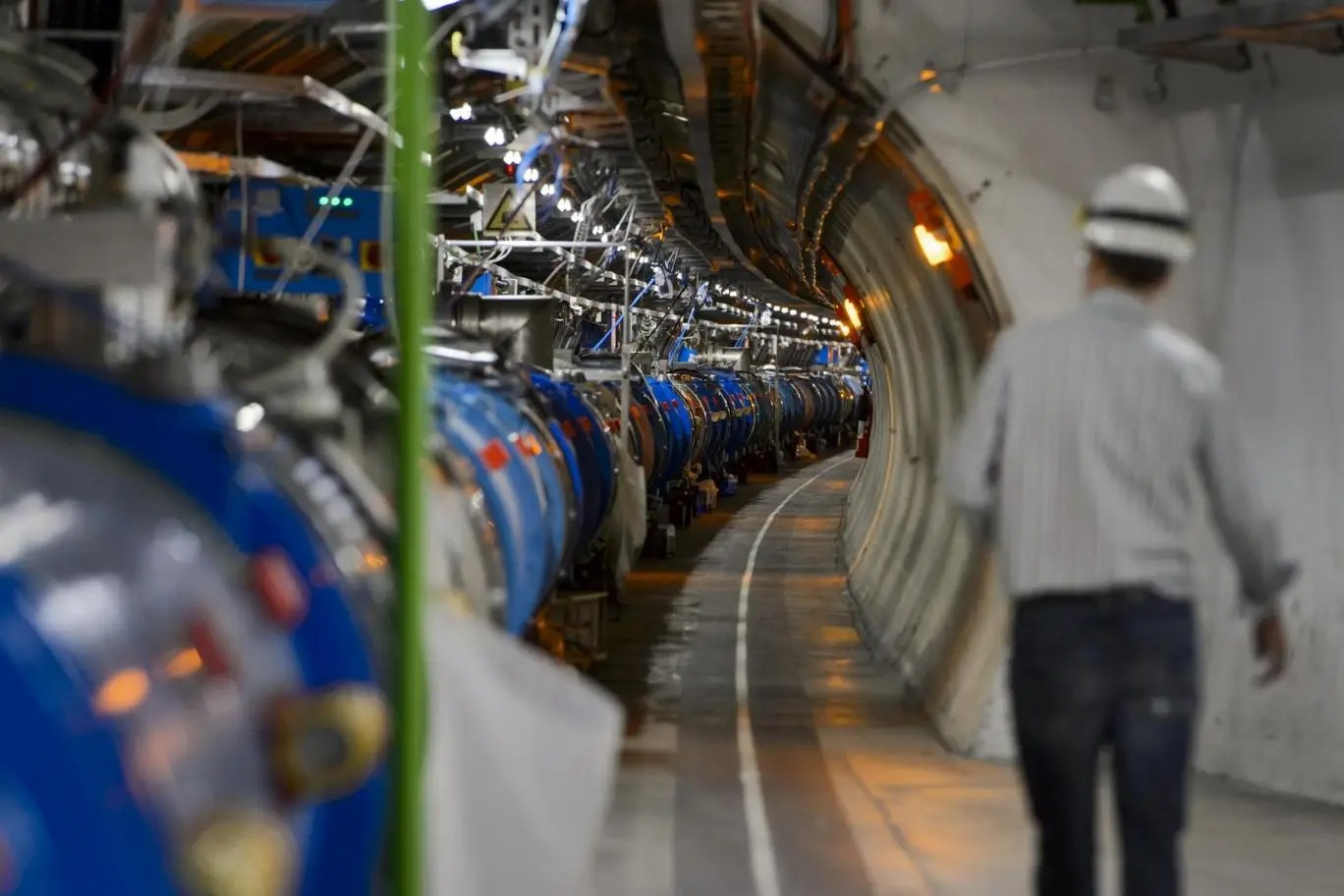 A scientist walks along a tunnel containing the Large Hadron Collider