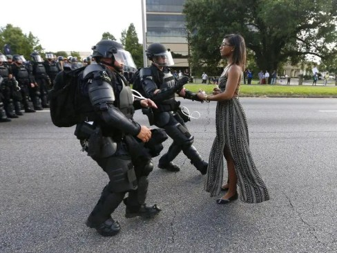Photo of two police dressed in black body armor charging at a skinny black girl standing calmly and non-threateningly
