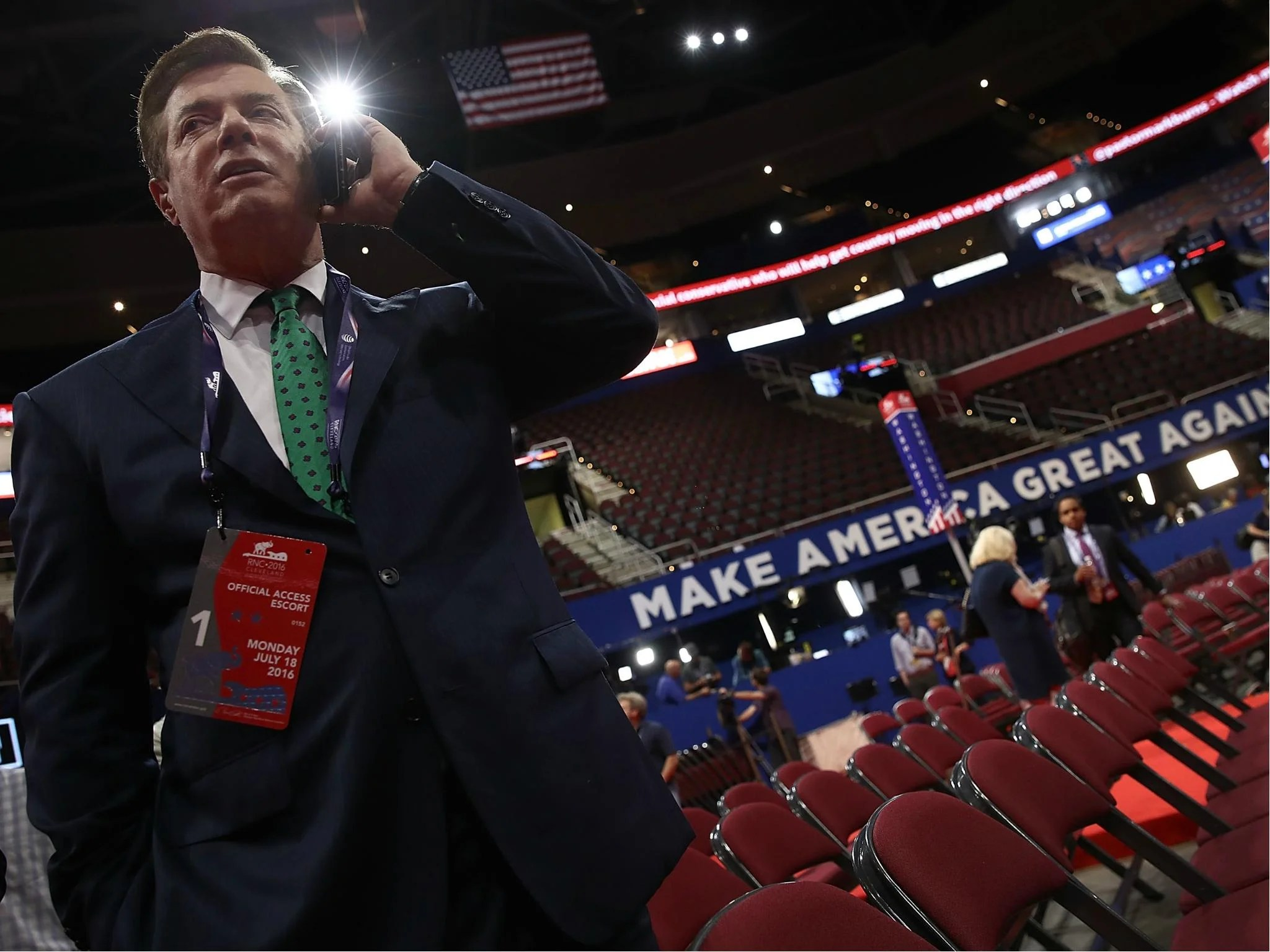 Paul Manafort, former campaign manager for President Donald Trump, speaks on the phone while touring the floor of the Republican National Convention 17 July 2016 in Cleveland, Ohio.