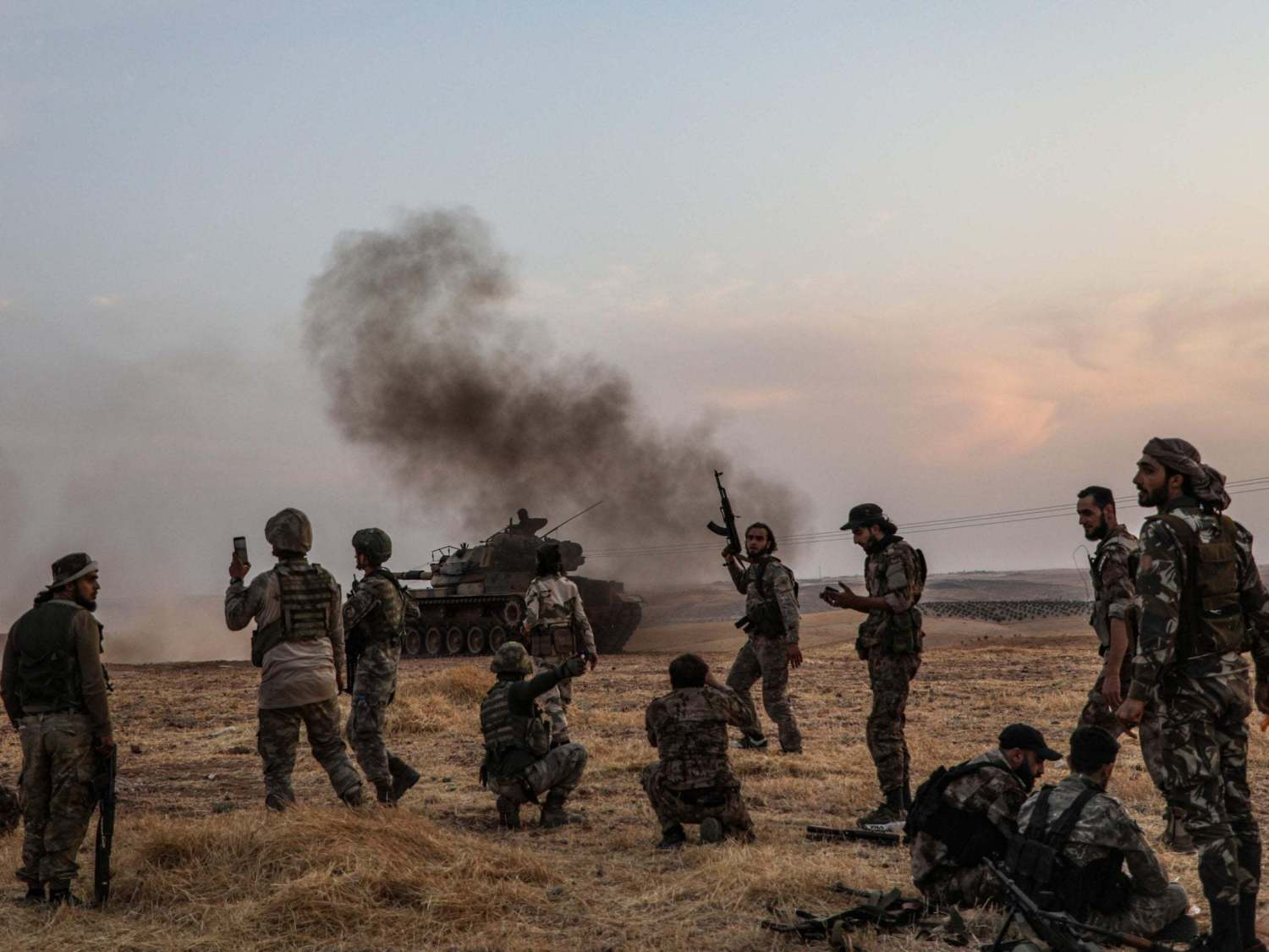 Turkish soldiers and Turkey-backed Syrian fighters gather on the northern outskirts of the Syrian city of Manbij in October
