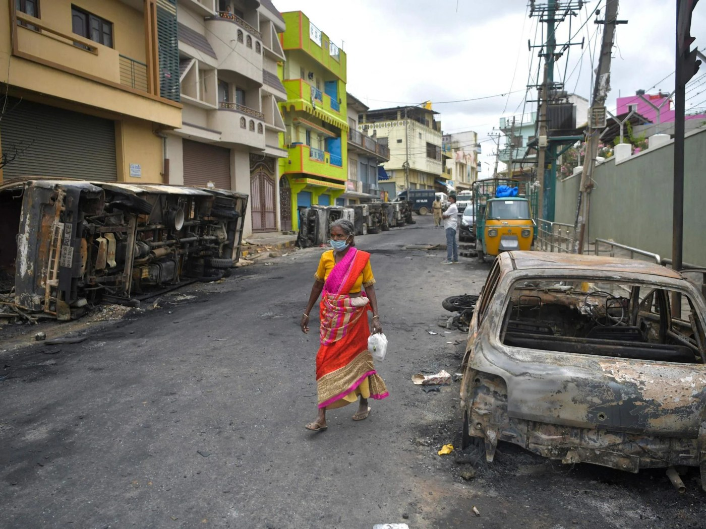 A resident walks past the burned-out remains of a car following protests in the city of Bengaluru, India, over a Facebook post about the Prophet Mohammed.