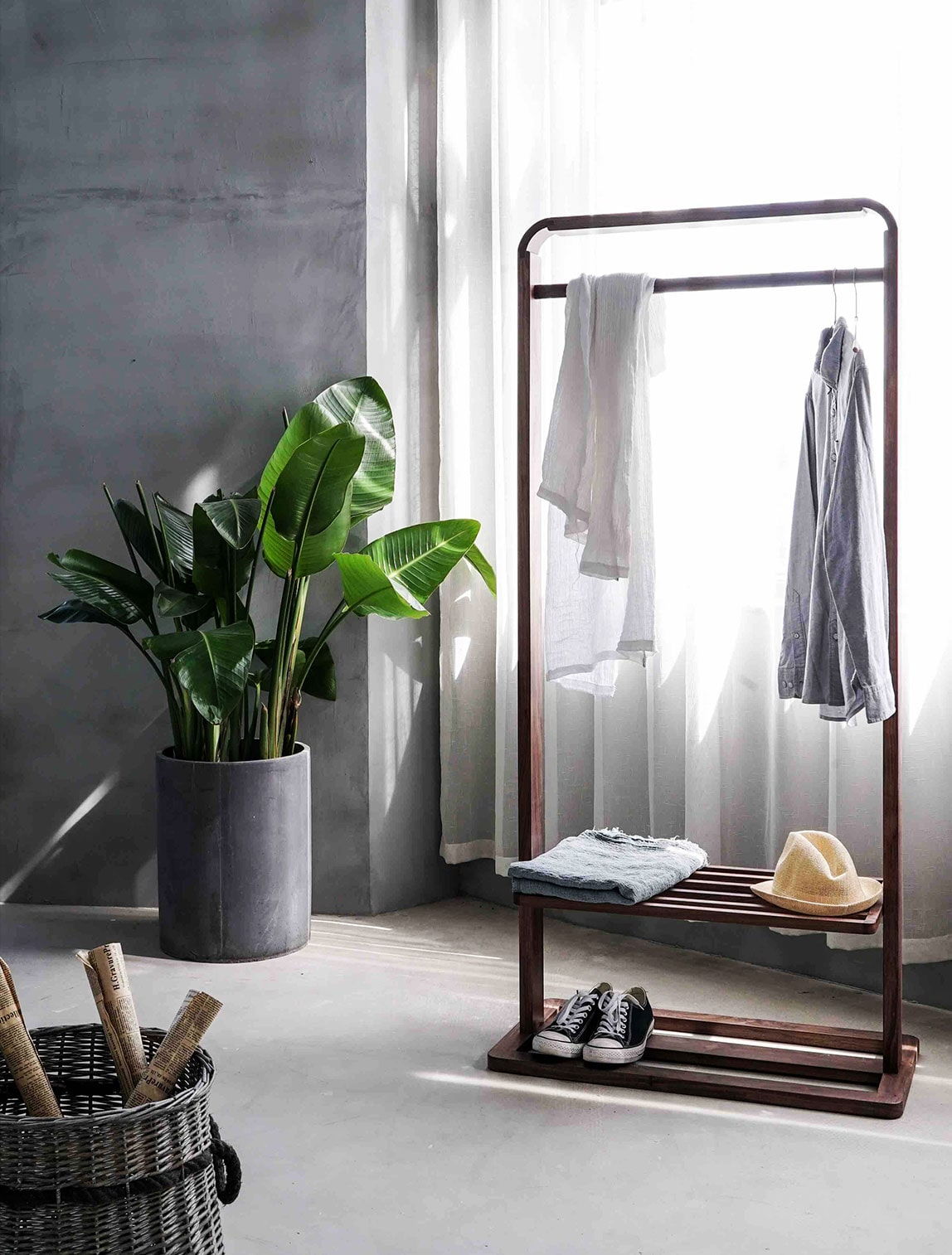 A modern bedroom featuring a clothing stand with two shirts, a fedora, a scarf and Converse shoes, a basket with rolled newspapers, a grey planter filled with greenery and white sheer curtains.