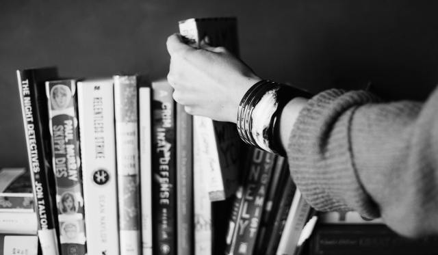 A black and white shot of a woman's hand pulling a book off a bookshelf.