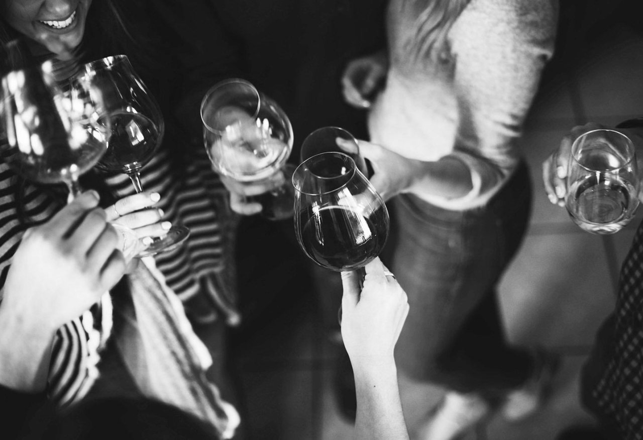 A black and white shot of a group of hands holding wine glasses, coming together to say cheers.