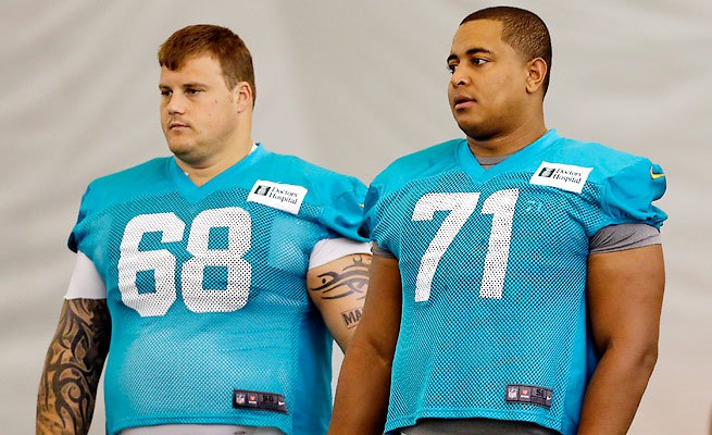 Two beefy football linemen standing side by side in their jerseys w/o helmets --Richie-incognito-jonathan-martin