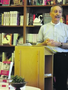 Karl Schonborn, standing at podium, talking at bookstore event.