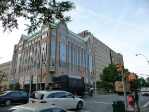 Large neo-modern 8 story bldg at busy street corner.