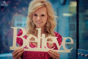 """Pretty young woman holding cut out word spelling """"Believe."""""""