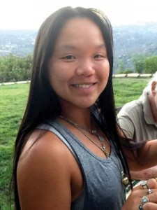 Asian girl with repaired cleft lip and palate smiling outdoors.