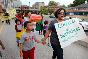 Woman holding hand of young child marching to end 'school-to-prison pipeline.'
