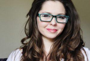 Headshot of brunette Amber Rose Carlson in glasses, who addresses rape & male privilege.